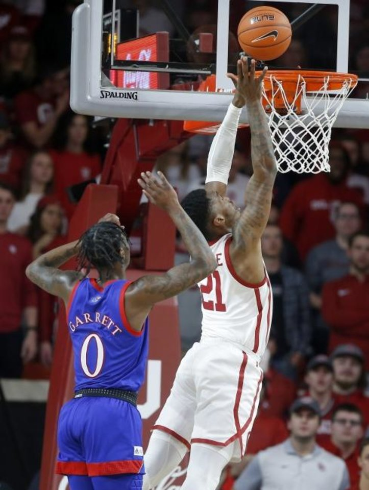 Photo -  Oklahoma's Kristian Doolittle, right, goes to the basket past Kansas' Marcus Garrett during Tuesday night's Big 12 basketball game at Lloyd Noble Center. [Bryan Terry/The Oklahoman]