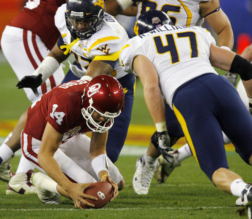 Photo - Sam Bradford (14) recovers a fumble caused by West Virginia's Reed Williams (47) during the first half of the Fiesta Bowl college football game between the University of Oklahoma Sooners (OU) and the West Virginia University Mountaineers (WVU) at The University of Phoenix Stadium on Wednesday, Jan. 2, 2008, in Glendale, Ariz. 