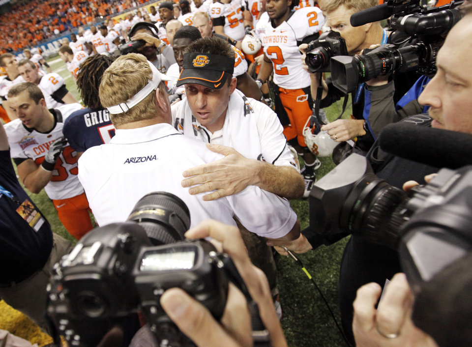 Photo - OSU head coach Mike Gundy and Arizona head coach Mike Stoops talk after the Valero Alamo Bowl college football game between the Oklahoma State University Cowboys (OSU) and the University of Arizona Wildcats at the Alamodome in San Antonio, Texas, Wednesday, December 29, 2010. OSU won, 36-10. Photo by Nate Billings, The Oklahoman