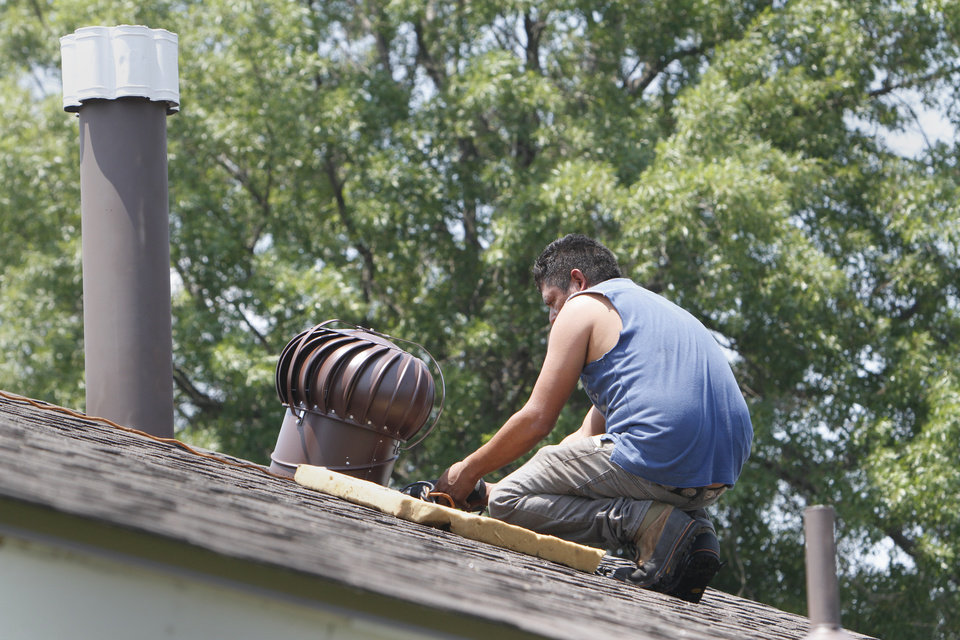 Photo -  Workers put the finishing touches on a new roof on the home of Sue Bridges.    David McDaniel -  The Oklahoman