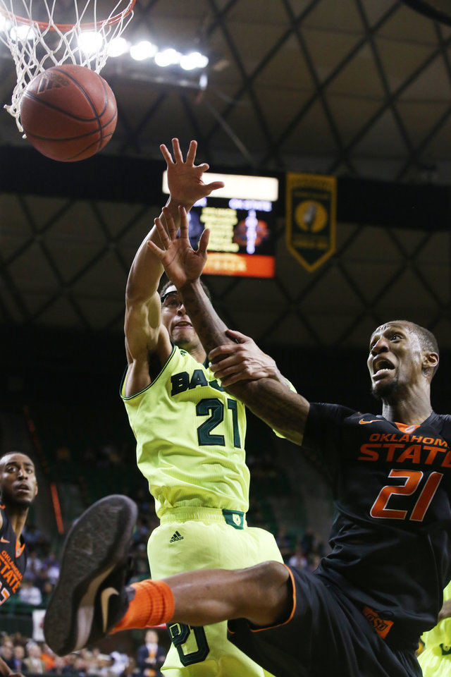 Photo - Baylor center Isaiah Austin (21), left, grabs the arm of Oklahoma State forward/center Kamari Murphy (21), right, in the second half of an NCAA college basketball game, Monday, Feb. 17, 2014, in Waco, Texas. (AP Photo/Waco Tribune Herald, Rod Aydelotte)