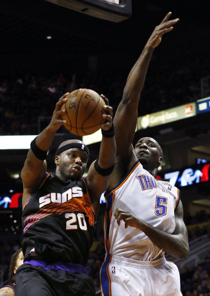 Photo - Phoenix Suns' Jermaine O'Neal (20) grabs a rebound in front of Oklahoma City Thunder's Kendrick Perkins (5) during the first half in an NBA basketball game Sunday, Feb. 10, 2013, in Phoenix.(AP Photo/Ross D. Franklin)