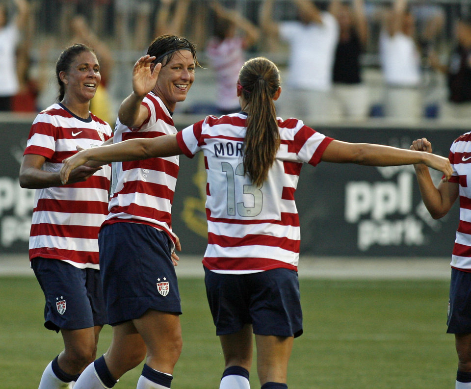 Photo -   United States' Abby Wambach, second from left, celebrates with Shannon Boxx, left, and Alex Morgan (13) after scoring against China during the first half of their international friendly soccer match in Chester, Pa., Sunday, May 27, 2012. (AP Photo/H. Rumph Jr.)