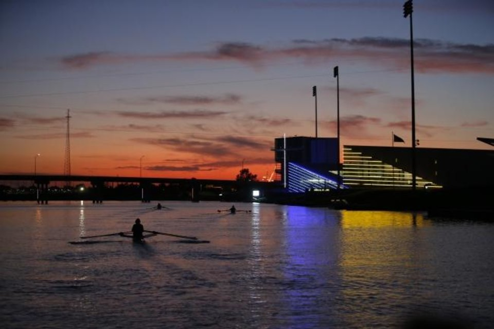 Photo -  Rowers practice as the sun sets on the Oklahoma River. Commercial development is being eyed as the next addition to the Boathouse District, lit up in this September photo. [Sarah Phipps/The Oklahoman]