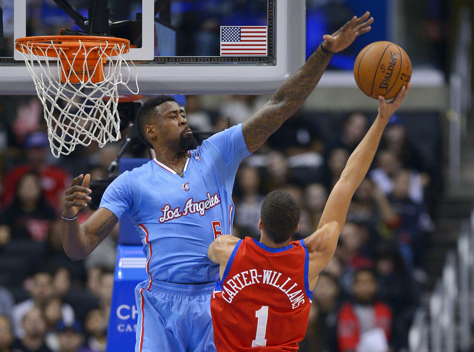 Photo - Los Angeles Clippers center DeAndre Jordan, left, rejects a shot by Philadelphia 76ers guard Michael Carter-Williams during the first half of an NBA basketball game Sunday, Feb. 9, 2014, in Los Angeles. (AP Photo/Mark J. Terrill)
