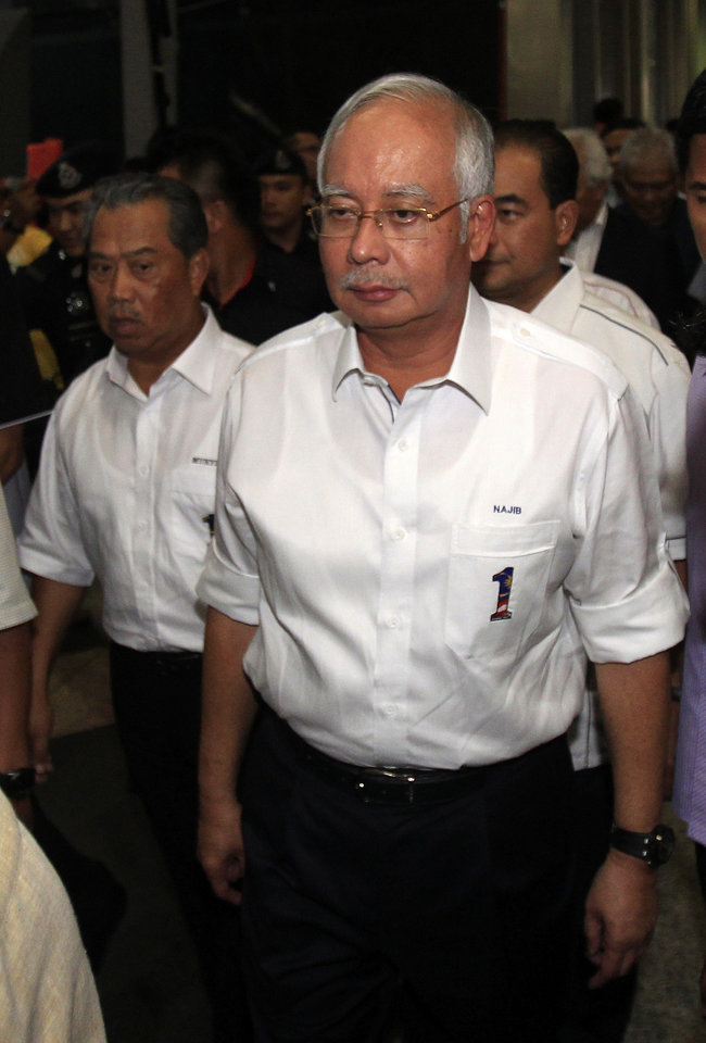 Photo - Malaysian Prime Minister Najib Razak, right, and his deputy Muhyiddin Yassin walk out of the reception center and holding area for family and friend of passengers aboard a missing Malaysia Airlines plane, at Kuala Lumpur International Airport in Sepang, outside Kuala Lumpur, Malaysia, Saturday, March 8, 2014. Search and rescue crews across Southeast Asia scrambled to find a Malaysia Airlines Boeing 777 that disappeared from air traffic control screens over waters between Malaysia and Vietnam early Saturday with 239 people aboard. (AP Photo/Lai Seng Sin)