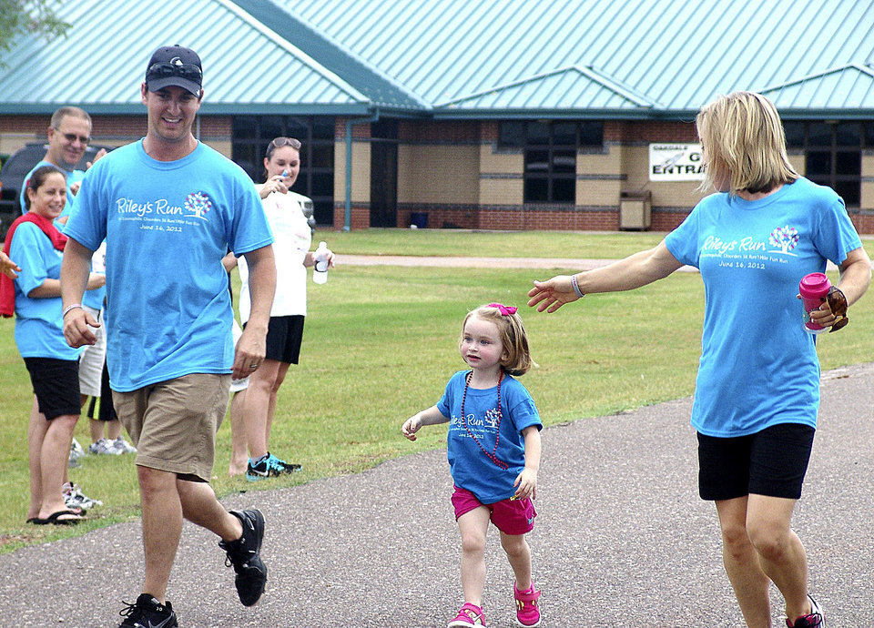 Photo - Riley Kahn, 3, and her parents Mike Kahn and Jill Kahn cross the finish line during the 1-mile fun run.  PHOTOS BY TIFFANY M. POOLE, FOR THE OKLAHOMAN