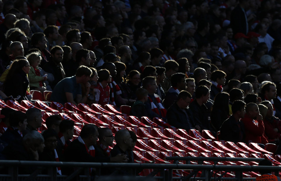 Photo - Supporters gather around 96 empty seats covered with Liverpool scarves in memory of the victims of the Hillsborough disaster, as they watch the English FA Cup semifinal soccer match between Wigan Athletic and Arsenal at Wembley Stadium in London, Saturday, April 12, 2014.  96 soccer supporters died and many more injured at the Hillsborough Stadium in Sheffield on April 15, 1989, during the FA Cup semifinal soccer match between Liverpool and Nottingham Forest. (AP Photo/Sang Tan)