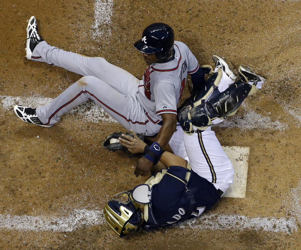 Milwaukee Brewers catcher Martin Maldonado, bottom, holds on to the ball as Atlanta Braves' B.J. Upton is forced out at second on a suicide squeeze by Julio Teheran during the fifth inning of a baseball game on Friday, June 21, 2013, in Milwaukee. (AP Photo/Morry Gash)