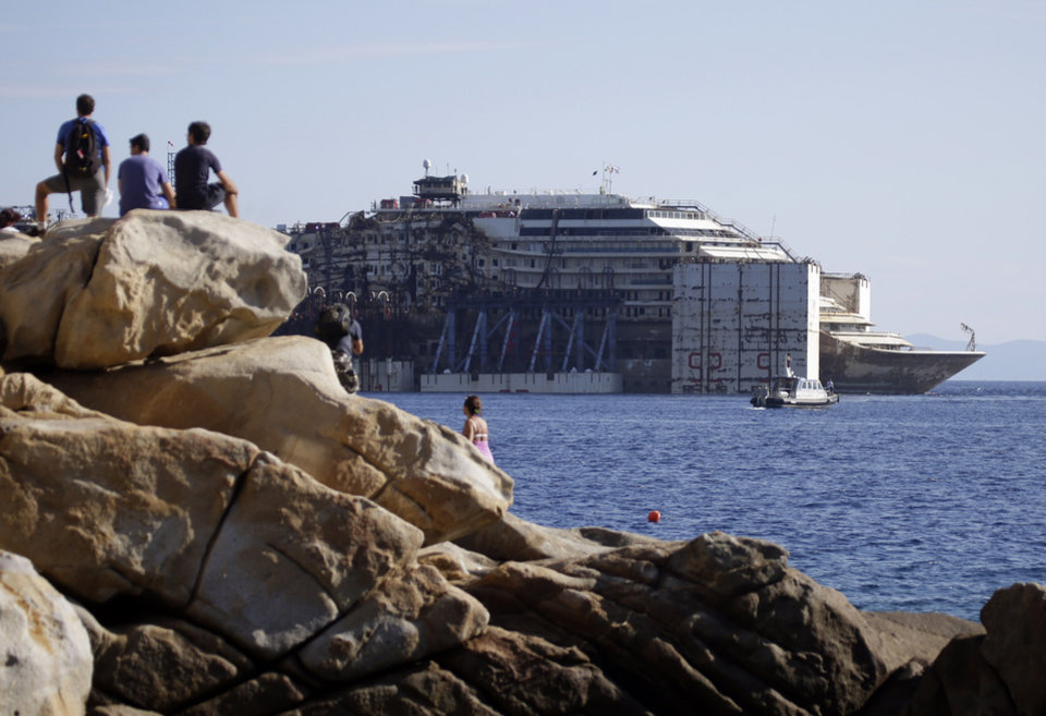 Photo - The Costa Concordia cruise wreck is towed away from the tiny Tuscan island of Isola del Giglio, Italy, Wednesday, July 23, 2014.  After more than two years since it slammed into a reef along the coastline of Isola del Giglio the wreck has begun its last journey, to the Italian port of Genoa, where it will be scrapped. 32 people died in the incident. (AP Photo/Gregorio Borgia)