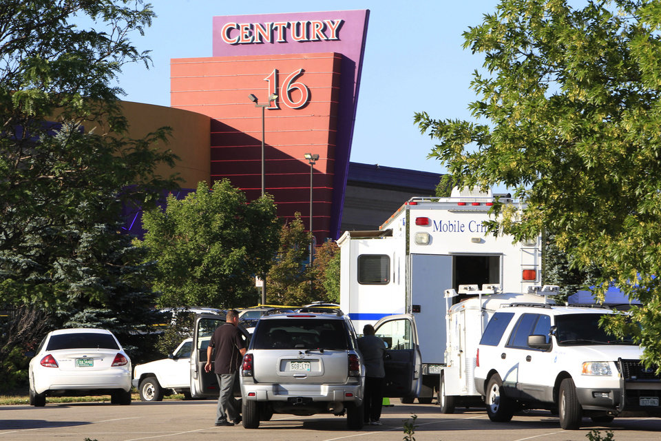 Photo - Police officers arrive at the Century 16 theatre east of the Aurora Mall in Aurora, Colo., on Friday, July 20, 2012.   A gunman wearing a gas mask set off an unknown gas and fired into the crowded movie theater killing 12 people and injuring at least 50 others, authorities said.  (AP Photo/David Zalubowski) ORG XMIT: CODZ101