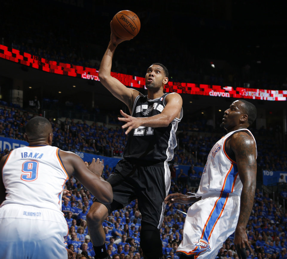Photo - San Antonio's Tim Duncan (21) goes up for a lay up in between Oklahoma City's Serge Ibaka (9) and Kendrick Perkins (5) during Game 3 of the Western Conference Finals in the NBA playoffs between the Oklahoma City Thunder and the San Antonio Spurs at Chesapeake Energy Arena in Oklahoma City, Sunday, May 25, 2014. Photo by Bryan Terry, The Oklahoman