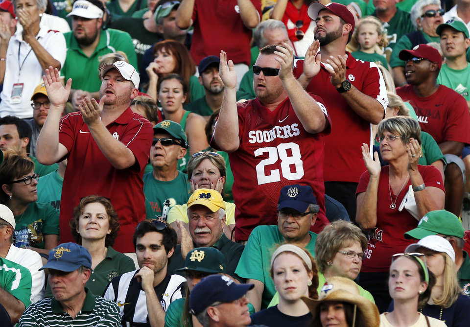 Photo - OU fans cheer among Notre Dame fans late in a college football game between the University of Oklahoma Sooners and the Notre Dame Fighting Irish at Notre Dame Stadium in South Bend, Ind., Saturday, Sept. 28, 2013. OU won, 35-21. Photo by Nate Billings, The Oklahoman