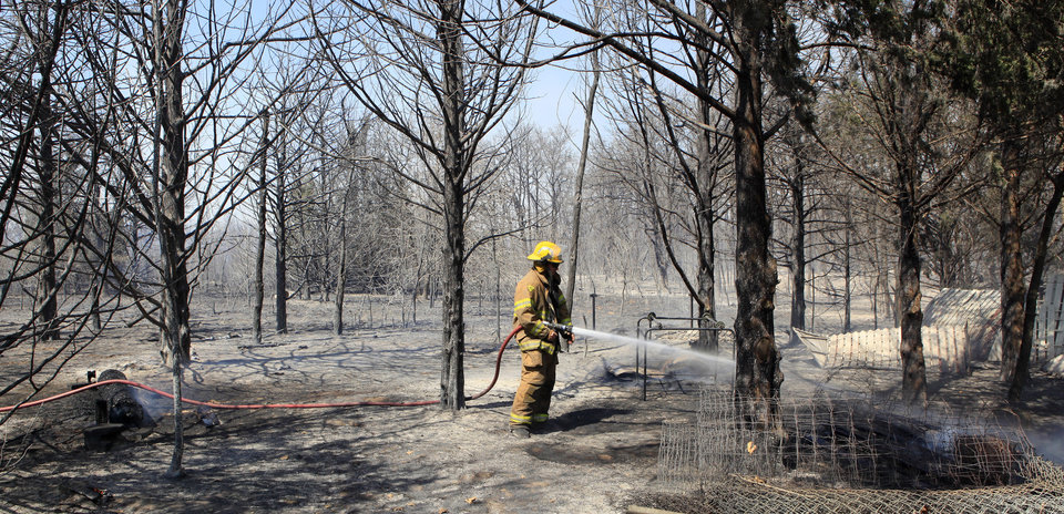 Photo - A firefighter putting out hot spots behind a home during a grass fire southeast of Post road and Wilshire in Oklahoma City Wednesday, April 6, 2011. Photo by Paul B. Southerland, The Oklahoman
