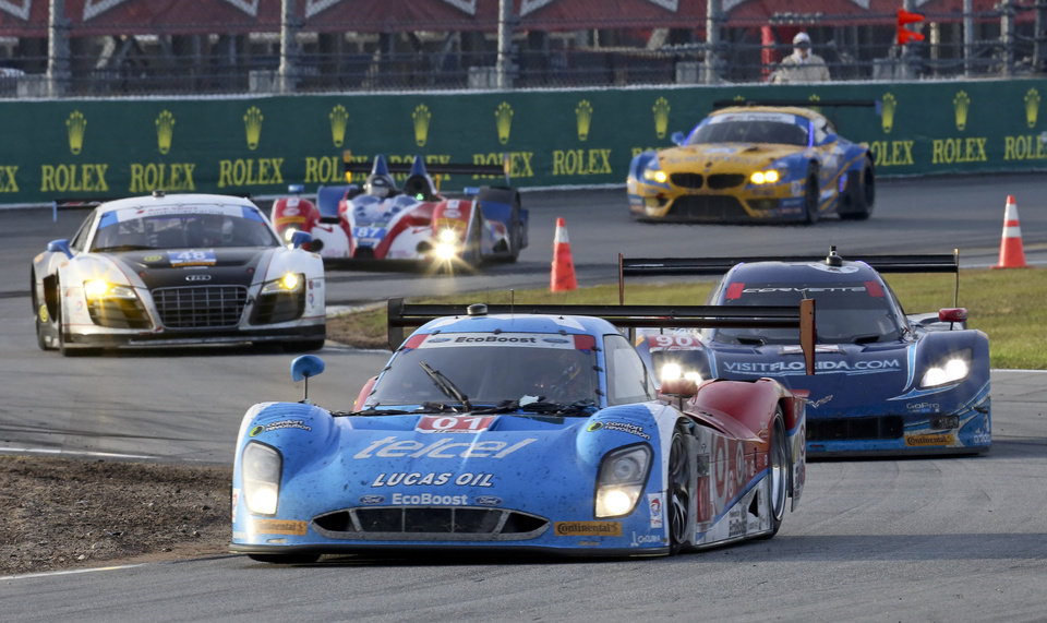 Photo - Cars race through the chicane led by the Ganassi Riley DP (01) during the IMSA Series Rolex 24 hour auto race at Daytona International Speedway in Daytona Beach, Fla., Sunday, Jan. 26, 2014.(AP Photo/David Graham)