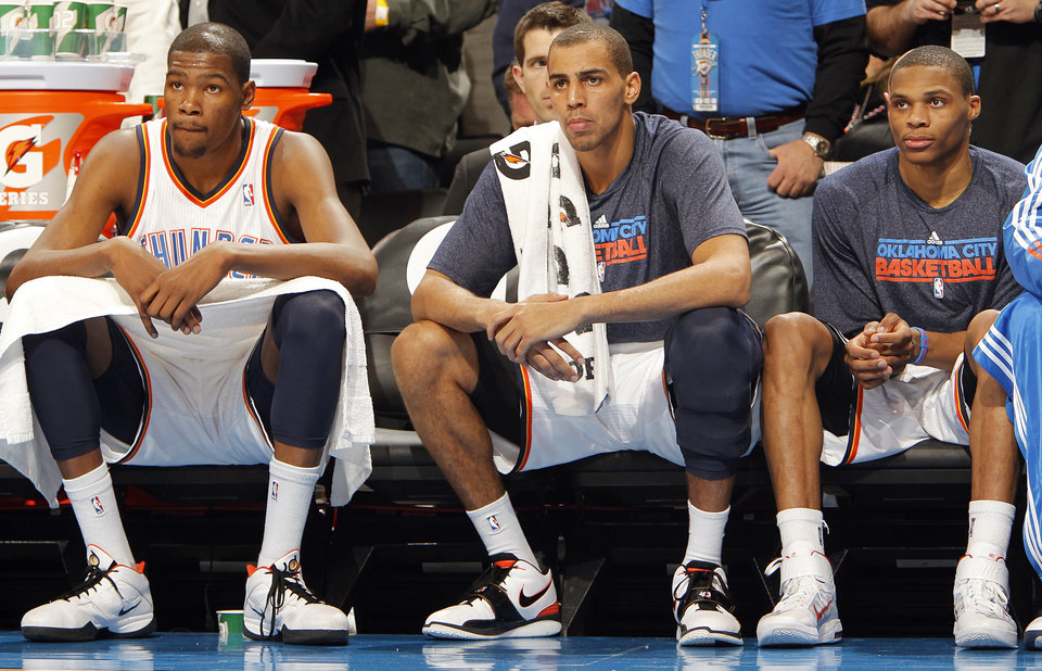The Thunder's Kevin Durant, Thabo Sefolosha, and Russell Westbrook, from left, look on from the bench in the second half during the NBA basketball game between the Oklahoma City Thunder and the Memphis Grizzlies at the Oklahoma City Arena on Tuesday, Feb. 8, 2011, Oklahoma City, Okla.