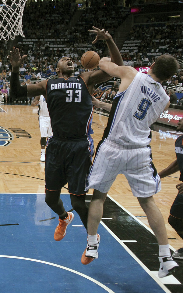 Charlotte Bobcats' Brendan Haywood (33) and Orlando Magic's Nikola Vucevic (9) vie for a rebound during the first half of an NBA basketball game, Friday, Jan. 18, 2013, in Orlando, Fla. (AP Photo/John Raoux)