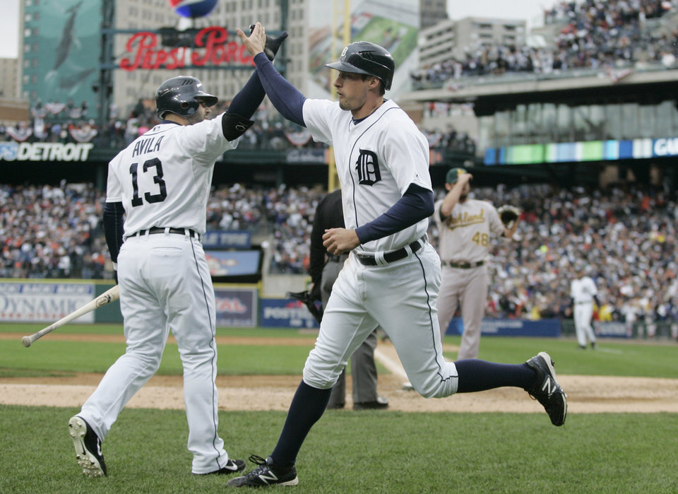 Detroit Tigers\' pinch runner Don Kelly, right, is met at the dugout by teammate Alex Avila after scoring on a wild pitch by Oakland Athletics relief pitcher Ryan Cook during the eighth inning of Game 2 of the American League division baseball series, Sunday, Oct. 7, 2012, in Detroit. (AP Photo/Duane Burleson)