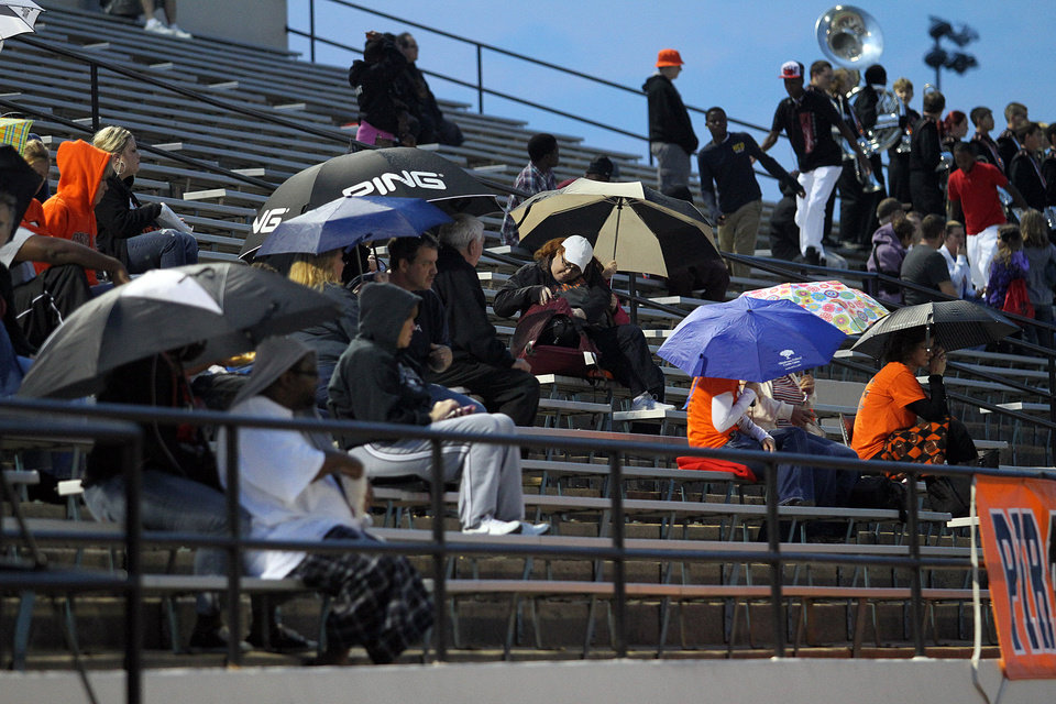 Photo - Fans sit under umbrellas as rain begins to fall during Putnam City - Broken Arrow high school football game at Putnam City Stadium Friday night. PHOTO BY HUGH SCOTT FOR THE OKLAHOMAN ORG XMIT: KOD