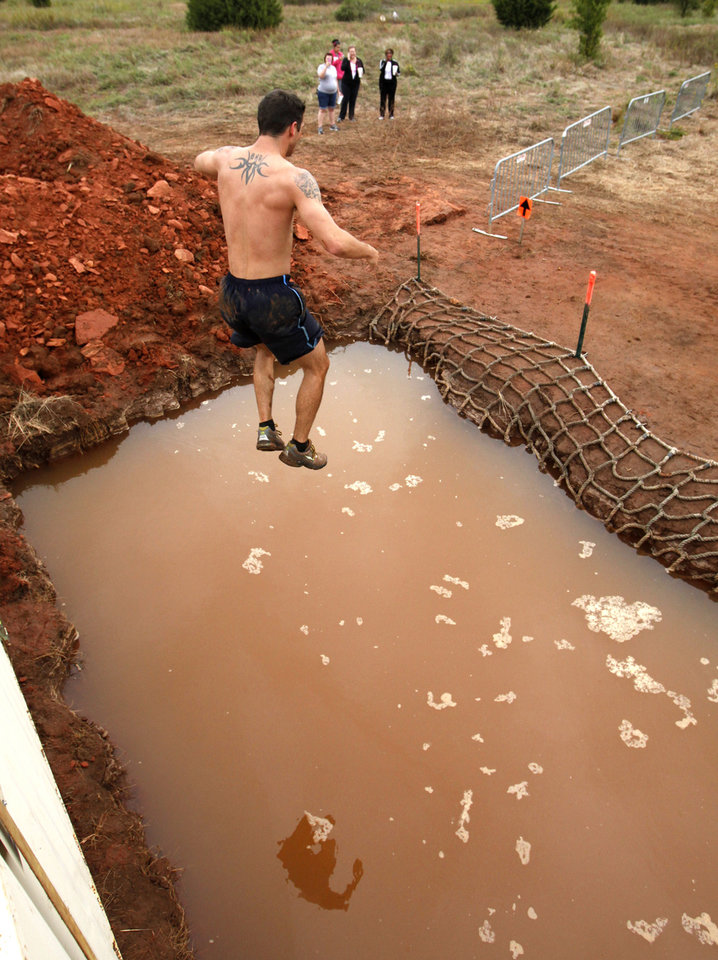 Brock Neely jumps from a nine foot platform into a pit in the Juggernaut mud run at Mitch Park, in Edmond, OK, Saturday, September 29, 2012. The Juggernaut is part of a national mud run series to raise money for Susan G. Komen for the Cure. By Paul Hellstern, The Oklahoman