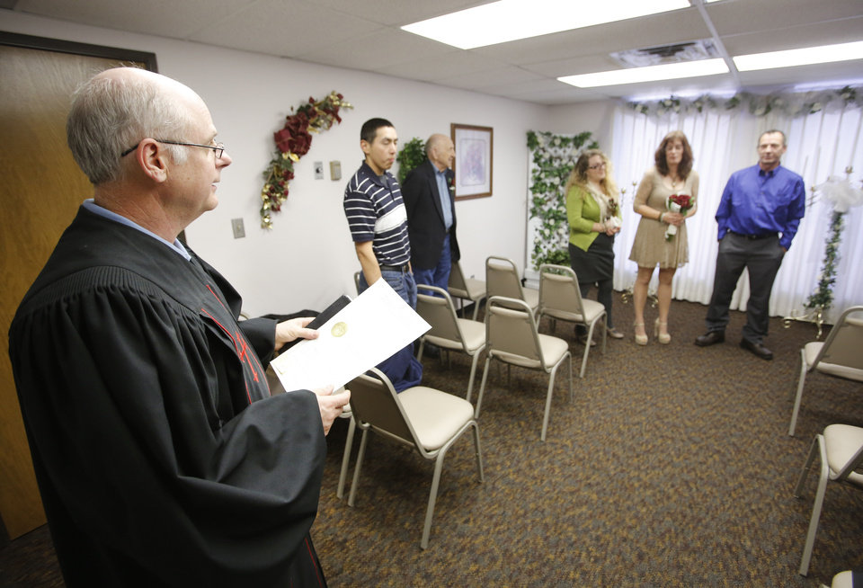 Jerry Freeland, left, officiates the wedding service for Tammie and Roger Lockwood at the Courthouse Lab & Wedding Chapel in Oklahoma City, Wednesday December 12, 2012. Dozens of couples decided to Tie The Knot on 12-12-12. Photo By Steve Gooch, The Oklahoman
