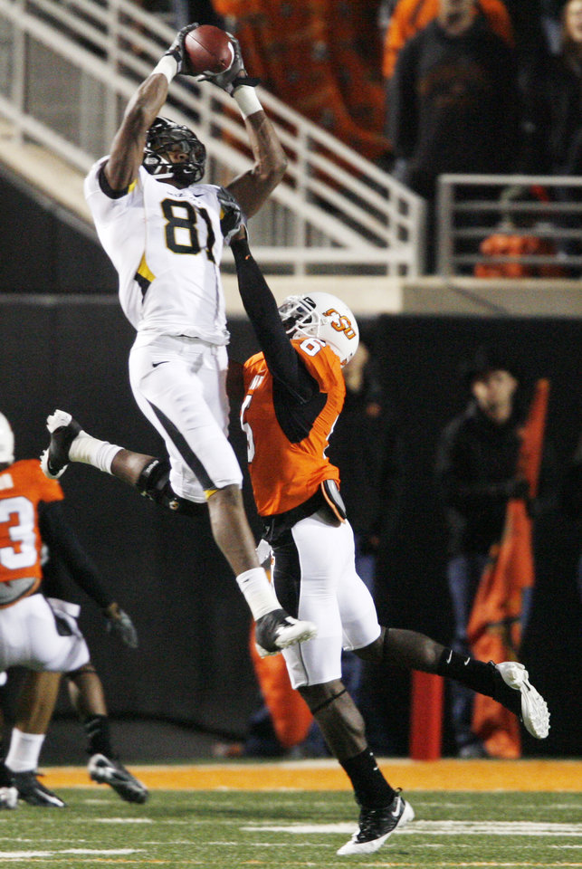 Photo - Danario Alexander (81) catches a pass over Perrish Cox (16) during the college football game between Oklahoma State University (OSU) and the University of Missouri (MU) at Boone Pickens Stadium in Stillwater, Okla. Saturday, Oct. 17, 2009.  Photo by Steve Sisney, The Oklahoman