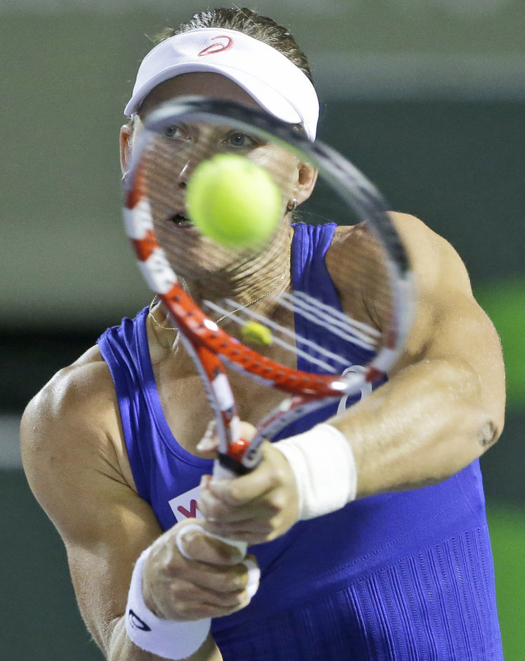 Photo - Samantha Stosur, of Australia, returns a shot from Coco Vandeweghe, of the United States, at the Sony Open tennis tournament, early Sunday, March 23, 2014, in Key Biscayne, Fla. (AP Photo/Wilfredo Lee)