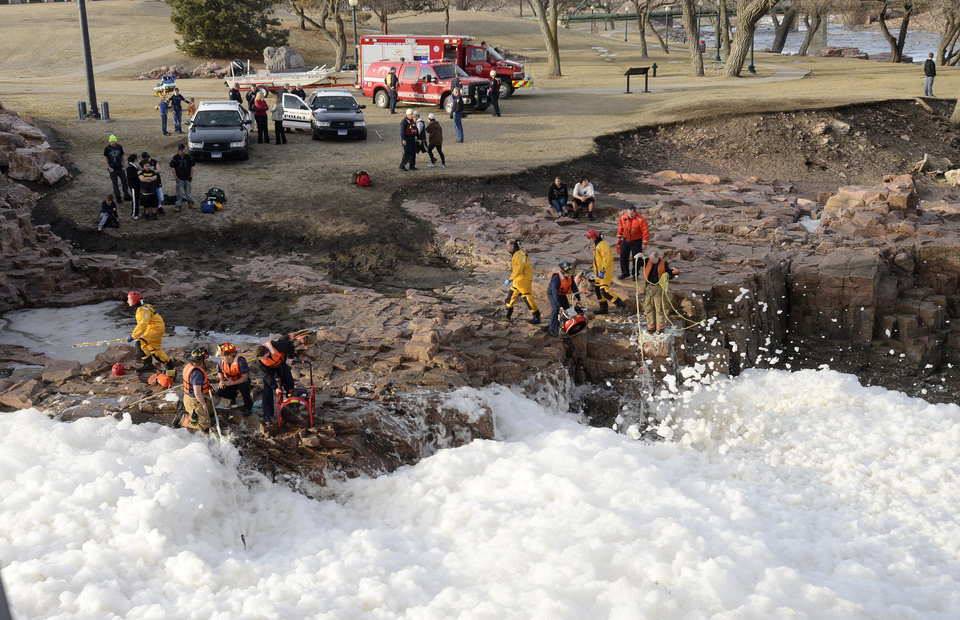Photo - Rescuers search the Big Sioux River for 16-year-old Madison Leigh Wallace and 28-year-old Lyle Francis Eagletail, who were dragged away by the fast-moving, icy river in Sioux Falls, S.D., as they tried to save the girl's 6-year-old brother, Garrett, Thursday, March 14, 2013. The boy was pulled ashore with minor injuries, but his sister and Eagletail are presumed drowned. (AP Photo/The Argus Leader, Elisha Page)  NO SALES