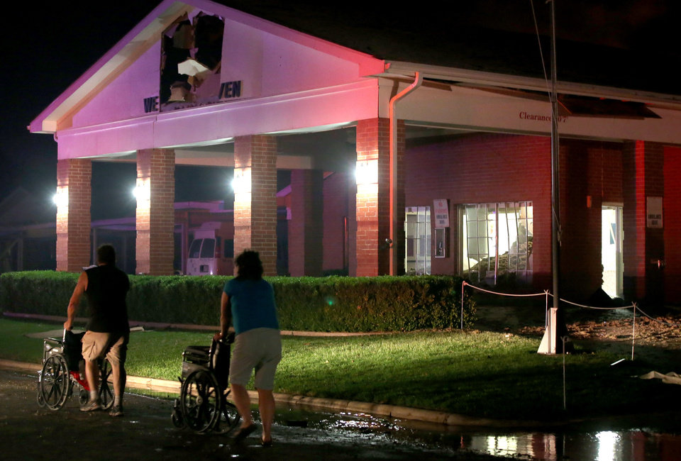 Photo - Persons are seen pushing wheel chairs in front of a damaged nursing home following an explosion at a nearby fertilizer plant Wednesday, April 17, 2013, in West, Texas. An explosion at a fertilizer plant near Waco caused numerous injuries and sent flames shooting high into the night sky on Wednesday.(AP Photo/ Waco Tribune Herald, Rod Aydelotte)
