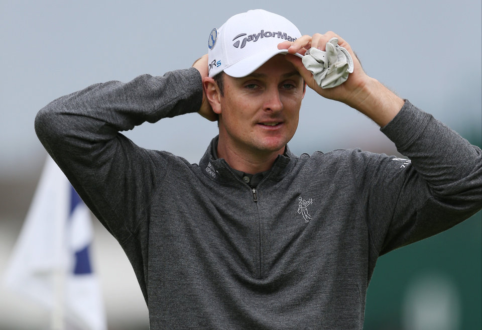 Photo - Justin Rose of England adjusts his hat on the 18th green as he finishes his practice round ahead of the British Open Golf championship at the Royal Liverpool golf club, Hoylake, England, Wednesday July 16, 2014. The British Open Golf championship starts Thursday July 17. (AP Photo/Jon Super)