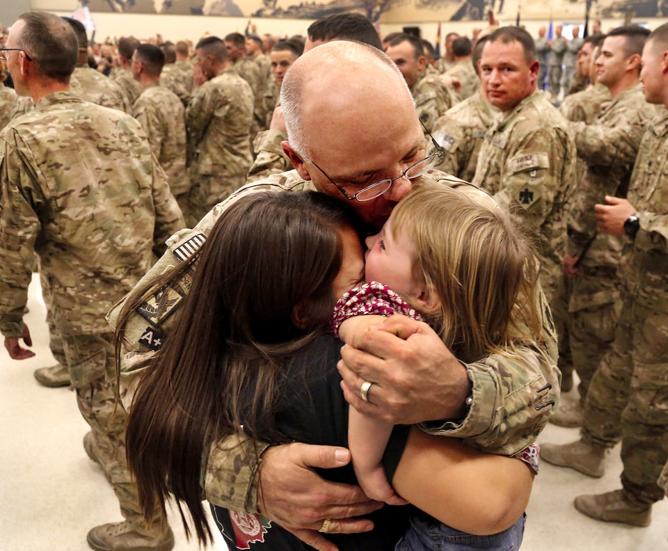 Photo - As soon as the troops were officially dismissed this woman and young girl raced to give this soldier hugs and kisses to welcome him home. At least 1,000 people, mostly spouses, children, relatives and friends, crowded into a large room in the Armed Forces Reserve Center in Norman on Saturday, Sep. 28, 2013, to give a boisterous, and at times, tearful welcome  to members of the Oklahoma National Guard who returned to Norman after 10 months in Afghanistan. After a brief ceremony, which included a personal thank-you to his troops from Maj. Gen. Myles Deering, the soldiers were dismissed to an emotional reunion with their love ones. Deering serves as adjutant general of Oklahoma.  Photo  by Jim Beckel, The Oklahoman.