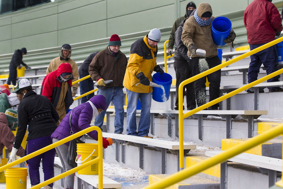 Photo - Workers clear ice and snow from the seats at Lambeau Field on Friday, Jan. 3, 2014, in Green Bay, Wis. in preparation for Sunday's NFL football wild-card playoff game between the Green Bay Packers and San Francisco 49ers. (AP Photo/Mike Roemer)