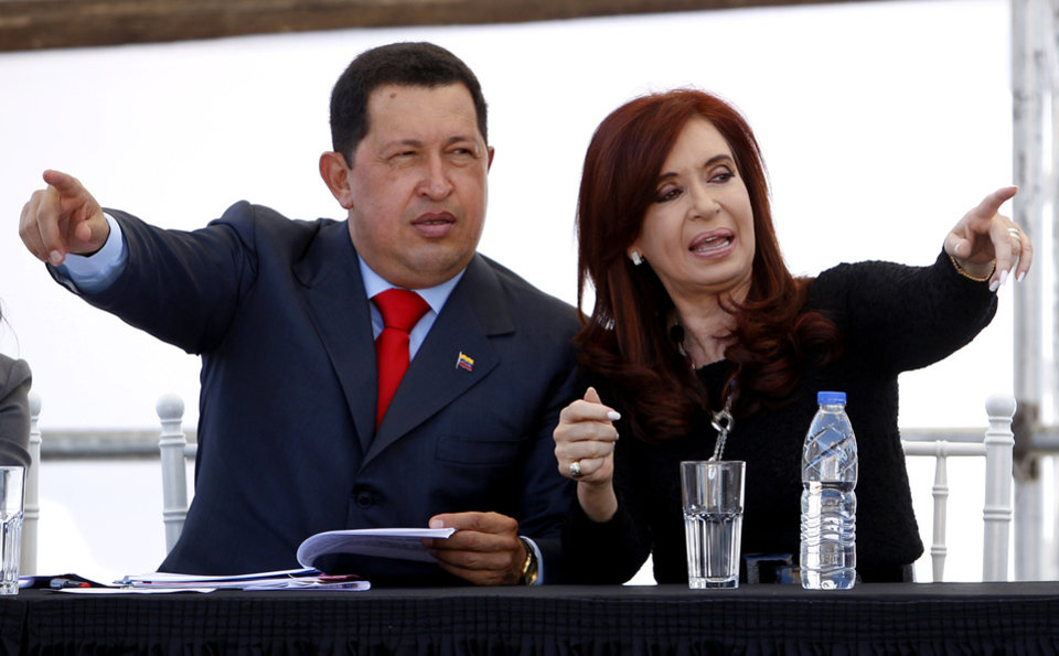 FILE - In this March 29, 2011 file photo, Venezuela's President Hugo Chavez, left, and Argentina's President Cristina Fernandez gesture before signing commercial accords during a visit to a state-run shipyard in Buenos Aires, Argentina. Fernandez is in Cuba on Friday, Jan. 11, 2013, to visit Chavez who is recovering from cancer surgery. The Venezuelan leader, normally at the center of national attention, is so ill following a fourth cancer surgery in Cuba that he has made no broadcast statement in more than a month, and has not appeared in a single photo. Officials have not specified what sort of cancer he suffers. (AP Photo/Natacha Pisarenko, File)