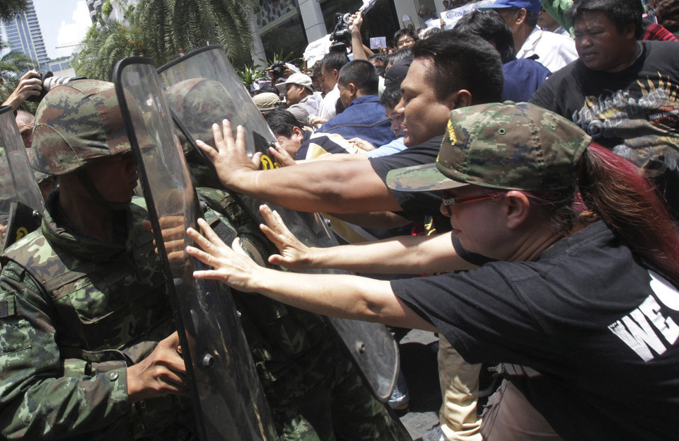 Photo - Protesters push Thai soldiers with shields during  an anti-coup demonstration in Bangkok, Thailand, Sunday, May 25, 2014. Gen. Prayuth Chan-ocha in Thailand's ruling junta warned people Sunday not to join anti-coup street protests, saying normal democratic principles cannot be applied at the time, as troops fanned out in central Bangkok to prevent rallies. (AP Photo/Sakchai Lalit)