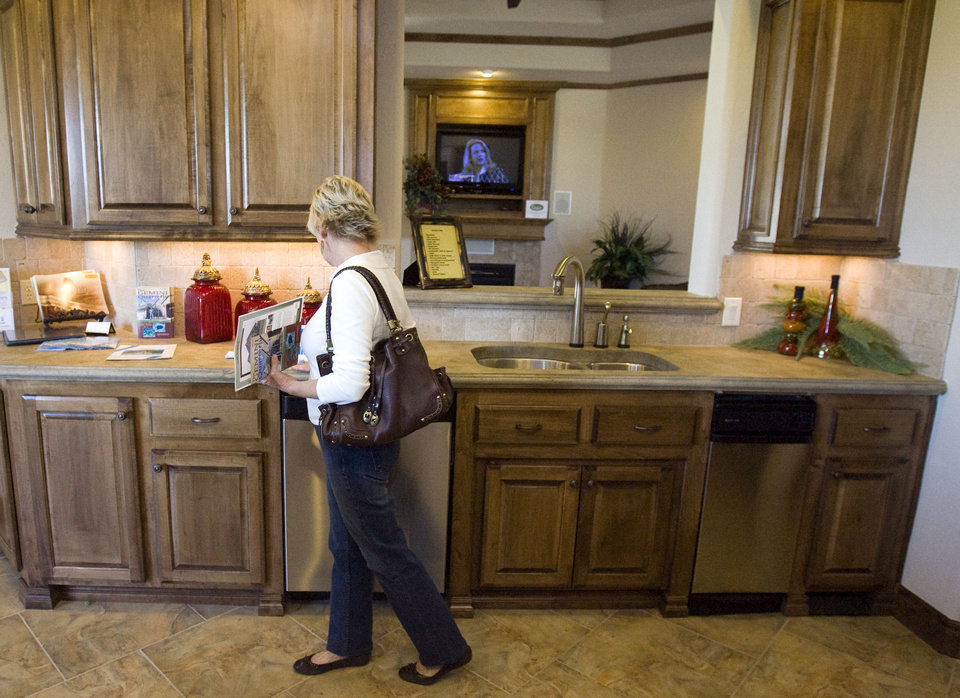 Carol Barnes of Lawton, Okla., looks at the counters in the kitchen of a home built by Josh Simmons in the Williamson Farms housing addition in Oklahoma City, Tuesday, September, 16, 2008. The house is part of the Parade of Homes. BY SARAH PHIPPS, THE OKLAHOMAN