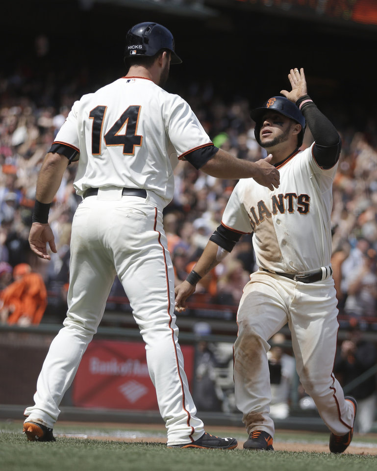 Photo - San Francisco Giants' Brandon Hicks (14) and Gregor Blanco celebrate after scoring against the Cleveland Indians in the fifth inning of a baseball game on Saturday, April 26, 2014, in San Francisco. They scored on a single hit by Hunter Pence. (AP Photo/Ben Margot)