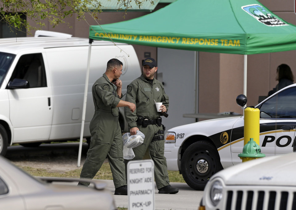 Members of the Orange County Sheriff's office walk by the entrance to the Tower 1 dorm at the University of Central Florida during an investigation Monday, March 18, 2013, in Orlando, Fla. University police investigating the apparent suicide of a student at the dorm discovered the explosives in his room. (AP Photo/John Raoux)