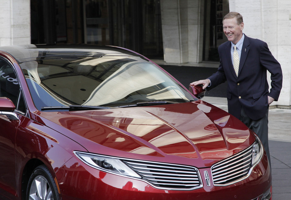 Photo - Ford Motor Co. President and CEO Alan Mulally laughs while standing next to a Lincoln MKZ during a press conference, Monday, Dec. 3, 2012 in New York. The MKZ will arrive at dealerships this month. The MKZ is the first of seven new or revamped Lincolns that will go on sale by 2015. (AP Photo/Mark Lennihan)