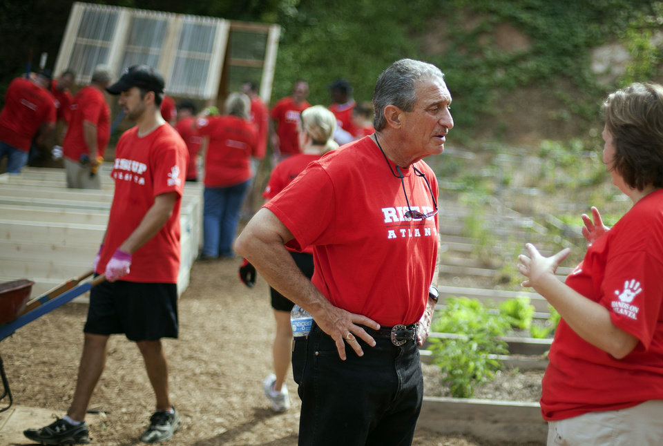 Photo -   Atlanta Falcons owner Arthur Blank, center, talks with Falcons director of human resources Karen Walters during a day of volunteering at the non-profit organization City of Refuge, Thursday, May 3, 2012, in Atlanta. Blank has paired his team with Hands On Atlanta, a community-based volunteer organization, in encouraging fans to give their time and energy to improve life in Atlanta. Blank and about 180 representatives of the Falcons and other of his businesses gathered to work on four key projects: constructing an indoor playground, planting an urban garden, remodeling resident dormitories, and painting an indoor mural. (AP Photo/David Goldman)
