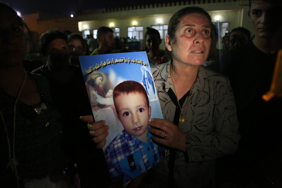 Photo - A displaced Iraqi Christian woman holds a picture of her four-year-old relative, David, who was killed by militants, at St. Joseph Church in Irbil, northern Iraq, Thursday, Aug. 7, 2014. Late Wednesday, militants overran a cluster of predominantly Christian villages alongside the country's semi-autonomous Kurdish region, sending tens of thousands of civilians and Kurdish fighters fleeing from the area, several priests in northern Iraq said Thursday. (AP Photo/Khalid Mohammed)