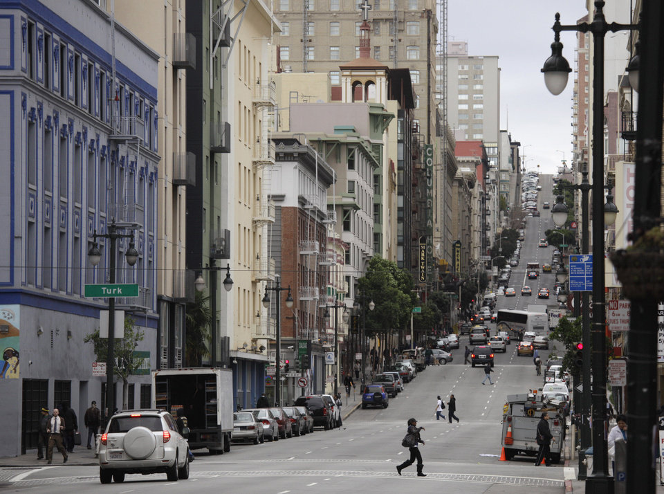 """Photo -   In this Feb. 15, 2011 file photo shown is a view looking up Taylor Street from Market Street in San Francisco. With Twitter's new headquarters set to open there soon, residents of a San Francisco neighborhood notorious for crime, drugs and homelessness remain among the least likely to have any way to send a tweet, much less access to basic goods and services. At a recent weekend """"hackathon,"""" engineers and entrepreneurs sought ways to use tech to help people in the Tenderloin and Mid-Market Street area find food, housing, healthcare and jobs. In the process, city leaders hope to ease tensions between needy locals and newly arriving startups flush with cash. (AP Photo/Eric Risberg, File)"""