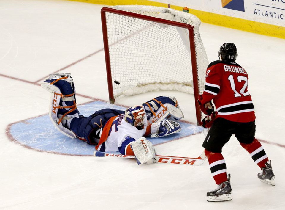 Photo - New Jersey Devils ring wing Damien Brunner (12), of the Czech Republic, scores a goal against New York Islanders goalie Anders Nilsson (45), of Sweden, during a shootout in an NHL hockey game on Friday, April 11, 2014, in Newark, N.J. The Islanders won 3-2. (AP Photo/Julio Cortez)