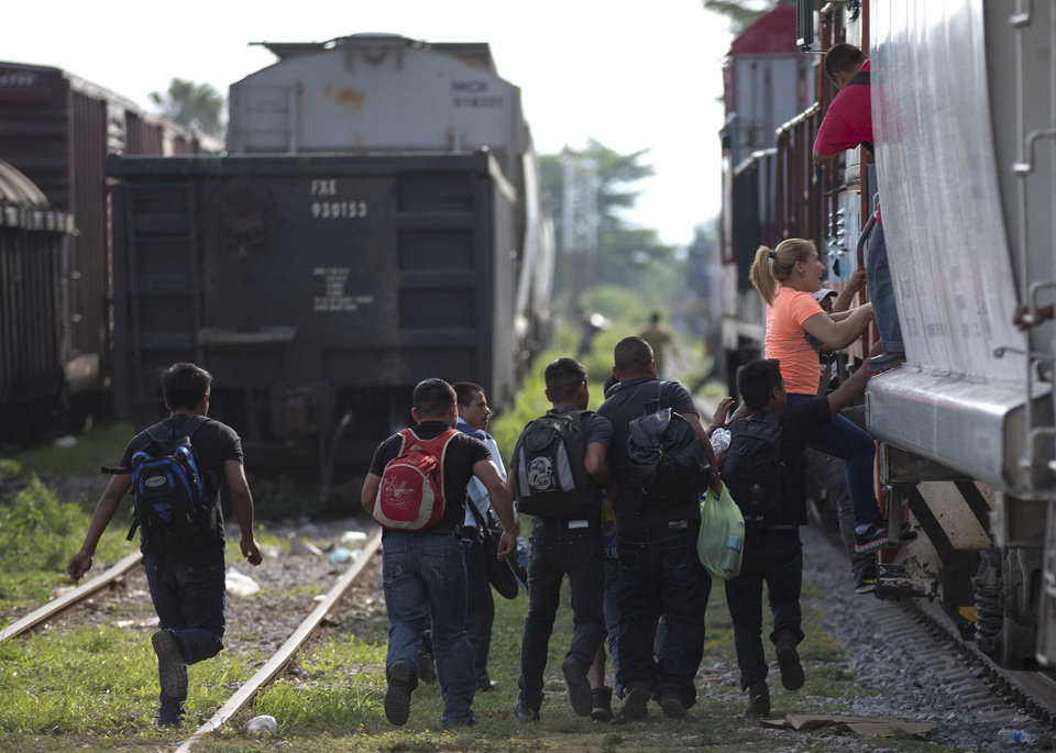 Photo - FILE - In this Saturday, July 12, 2014 file photo, immigrants run to jump on a train during their journey toward the U.S.-Mexico border, in Ixtepec, Mexico. Many of the immigrants recently flooding the nation's southern border say they're fleeing violent gangs in Central America. These gangs were a byproduct of U.S. immigration and Cold War policies, specifically growing from the increase in deportations in the 1990s. With weak dysfunctional governments at home, U.S. street gang culture easily took hold and flourished in these countries. (AP Photo/Eduardo Verdugo)