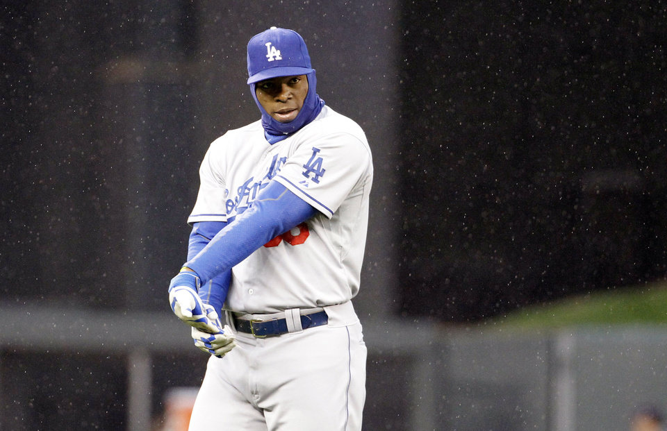 Photo - Los Angeles Dodgers right fielder Yasiel Puig warms up in a light rain before the first inning of a baseball game against the Minnesota Twins in Minneapolis, Wednesday, April 30, 2014. (AP Photo/Ann Heisenfelt)