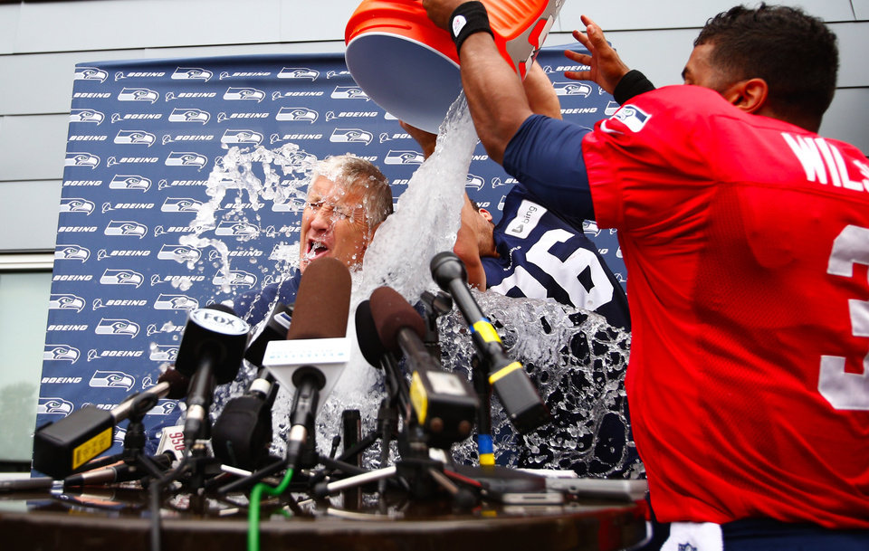 Photo - Seattle Seahawks players Russell Wilson, right, and Zach Mille dump ice water on their head coach Pete Carroll at the end of training camp at the Virginia Mason Athletic Center on Tuesday, Aug. 12, 2014, in Renton, Wash. They did it as part of the ALS Ice Bucket Challenge.   (AP Photo/The Seattle Times, John Lok)  SEATTLE OUT; USA TODAY OUT; MAGS OUT; TELEVISION OUT; NO SALES; MANDATORY CREDIT TO BOTH THE SEATTLE TIMES AND THE PHOTOGRAPHER