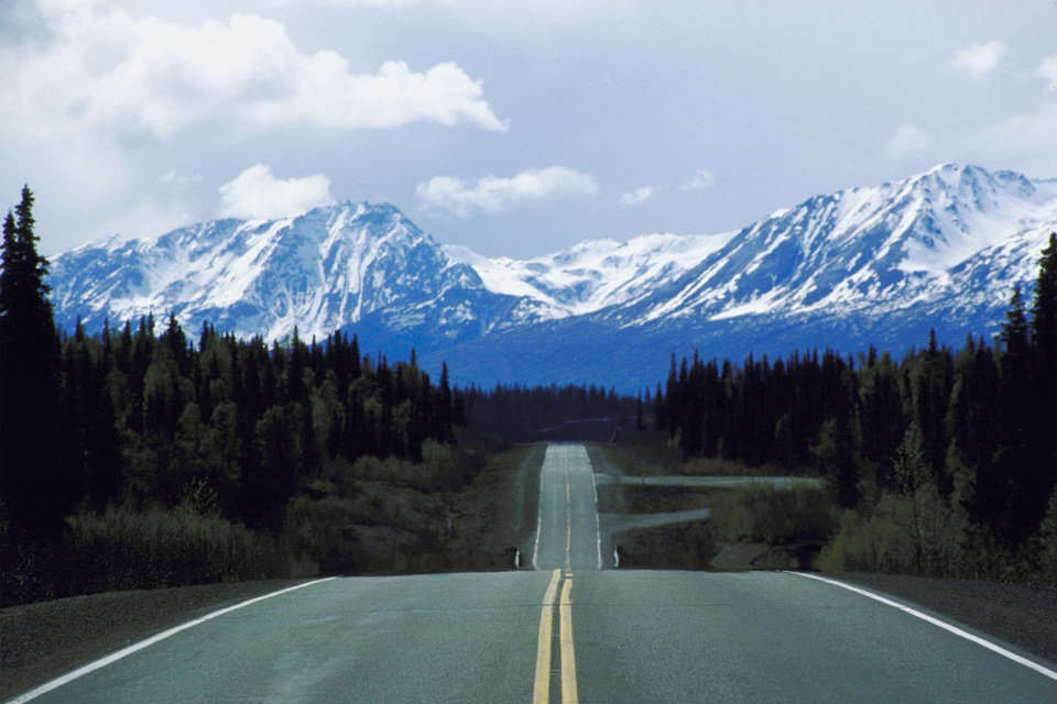 Snow-covered mountains provide excellent scenery as you travel Alaska highways. (Ablestock.com)