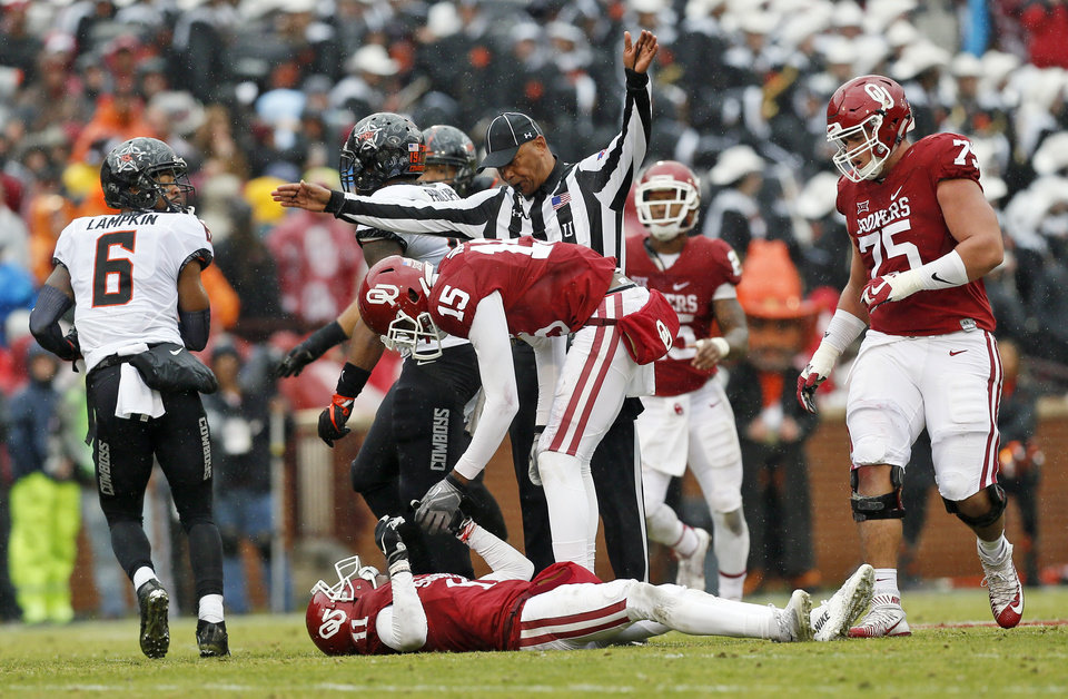 Photo - Oklahoma's Jeffery Mead (15) checks on Dede Westbrook (11) after he took a hard hit in the second quarter during the Bedlam college football game between the Oklahoma Sooners (OU) and the Oklahoma State Cowboys (OSU) at Gaylord Family - Oklahoma Memorial Stadium in Norman, Okla., Saturday, Dec. 3, 2016. Photo by Nate Billings, The Oklahoman