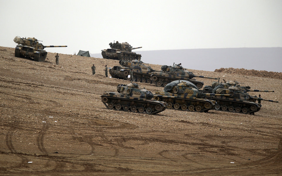 Photo - Turkish soldiers hold their positions with their tanks on a hilltop on the outskirts of Suruc, at the Turkey-Syria border, overlooking Kobani, Syria, during fighting between Syrian Kurds and the militants of Islamic State group, Sunday, Oct. 12, 2014. Kobani, also known as Ayn Arab, and its surrounding areas, has been under assault by extremists of the Islamic State group since mid-September and is being defended by Kurdish fighters.(AP Photo/Lefteris Pitarakis)