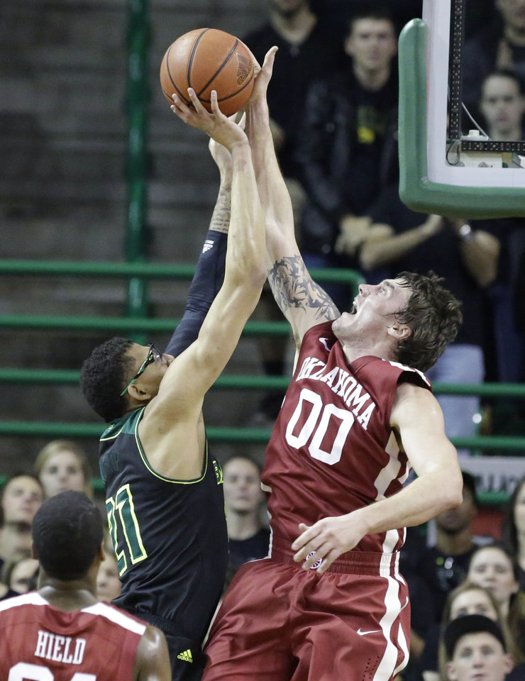 Photo - Oklahoma forward Ryan Spangler (00) blocks a shot by Baylor center Isaiah Austin (21) during the first half of an NCAA college basketball game Saturday, Jan. 18, 2014, in Waco, Texas. (AP Photo/LM Otero)