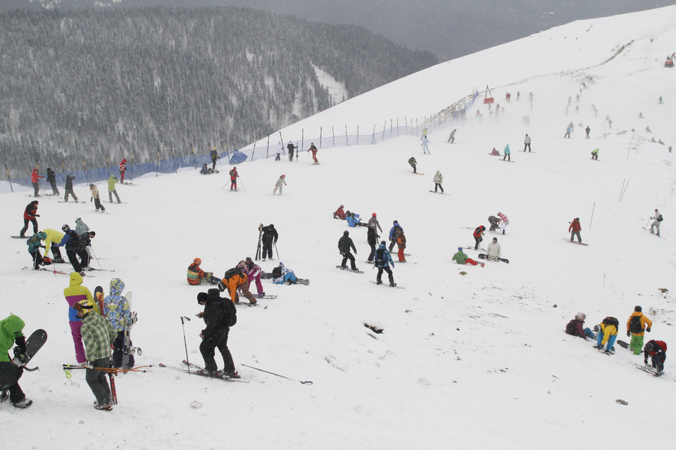 Photo - FOR STORY RUSSIA SOCHI YEAR TO GO - In this photo dated Saturday, Dec. 24, 2011, people enjoy snow at a ski resort in Krasnaya Polyana near the Black Sea resort of Sochi, southern Russia.  With just one year till the opening ceremony of the winter Olympic 2014 Sochi Games, the Black Sea resort of Sochi is a vast construction site sprawling for nearly 40 kilometers (25 miles) along the coast and 50 kilometers (30 miles) up into the mountains, with no escape from the clang and clatter of the construction works, the drilling, jack-hammering and mixing of cement. (AP Photo/Igor Yakunin)